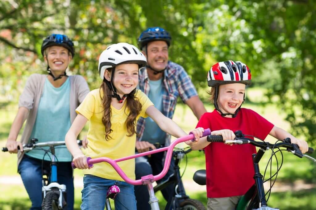 A happy family riding their bikes.