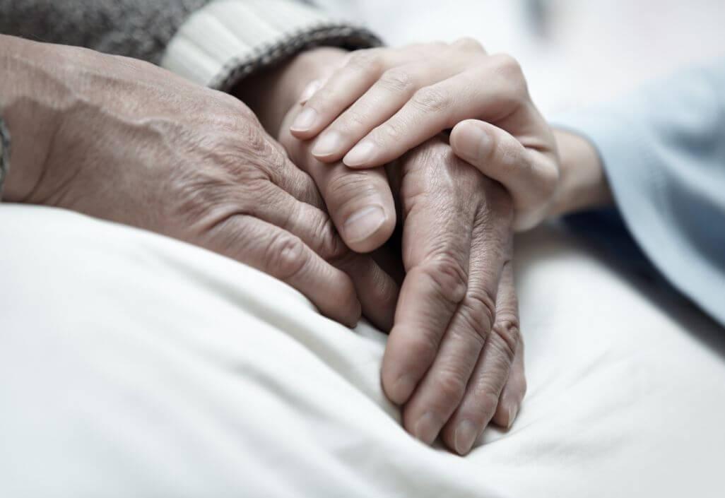A woman reassuring an elderly in a nursing home.