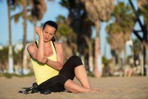 Injured woman sitting on a beach sand.